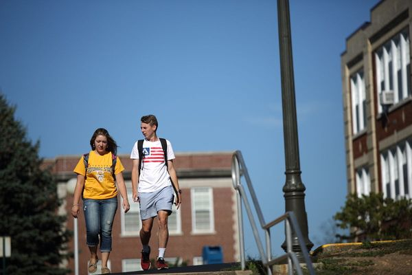 students walk across a college campus