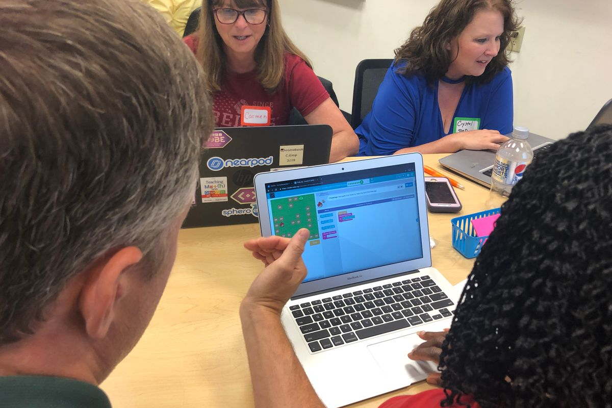 Factulty and students looking at a computer screen with the game Angry Birds on the screen