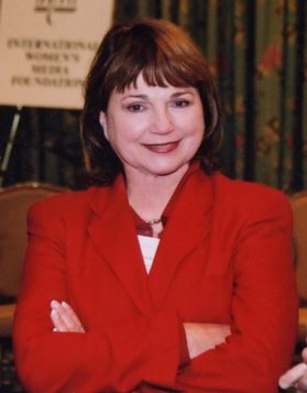 A woman wearing a red jacket, arms folded