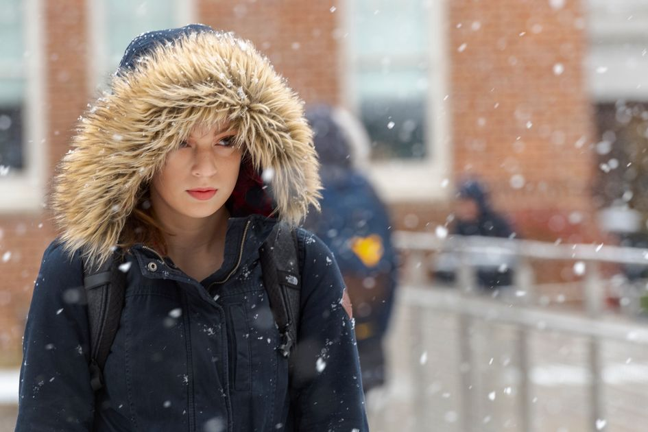 A girl in a coat with a fur hood walks in the snow