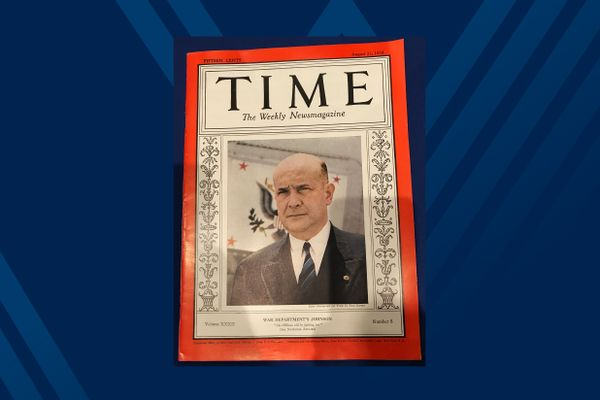 photo of TIME magazine cover with red border and man in dark blue suit
