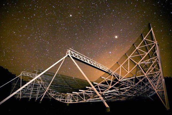 Large telescope under a starry night sky.