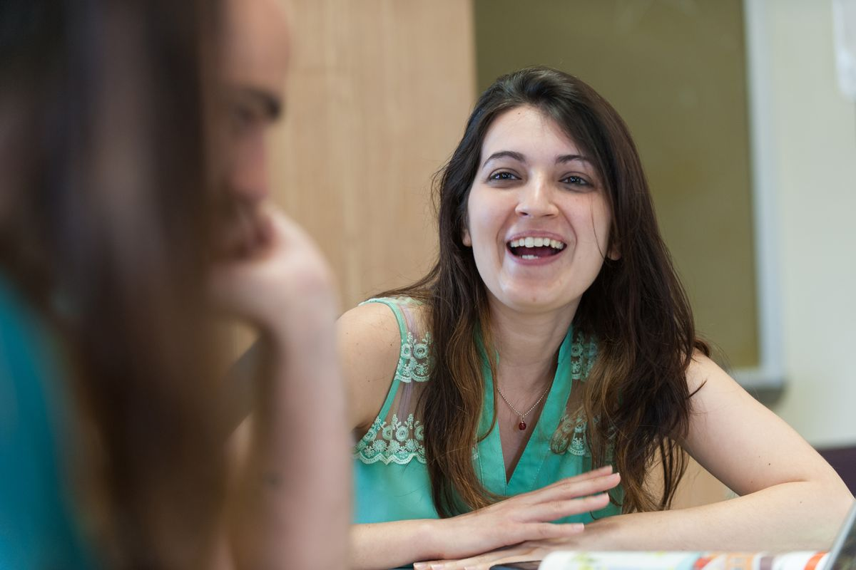 A woman with long dark hair and sleeveless aqua top smiling, arms crossed on table