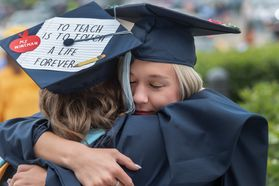 two women graduates hug