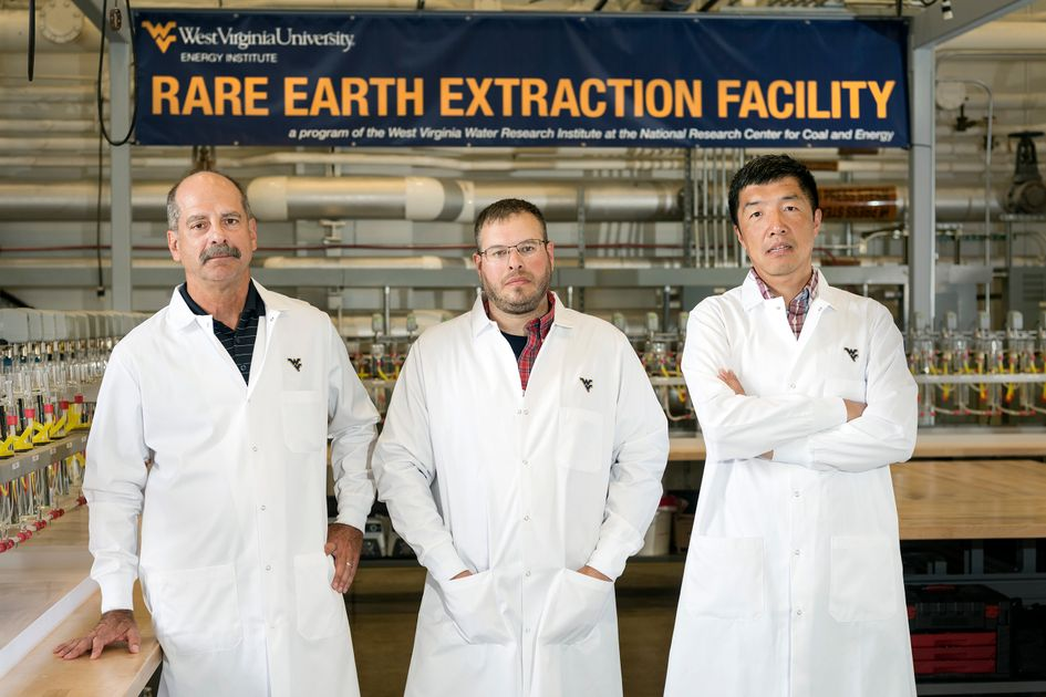 Three men in lab coats stand in front of the Rare Earth Extraction Facility sign