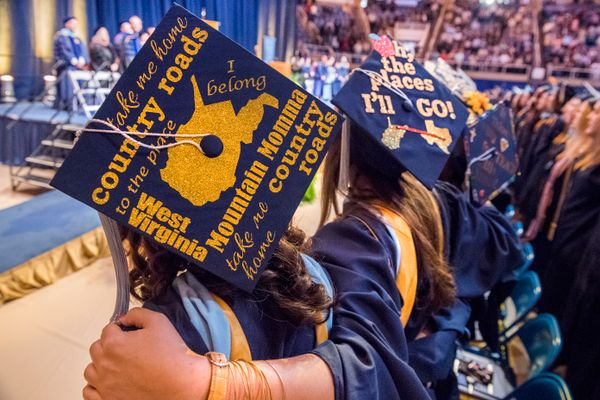 Students stand arm-in-arm during 2016 Commencement ceremony for the College of Education and Human Services