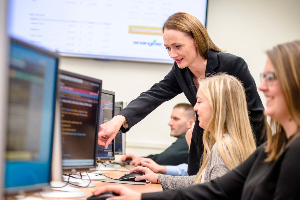photo of woman with long hair helping people at computer stations