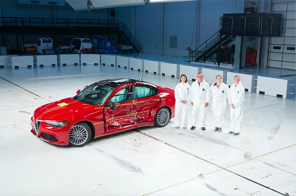 people dressed in white jump suits stand by shiny red car
