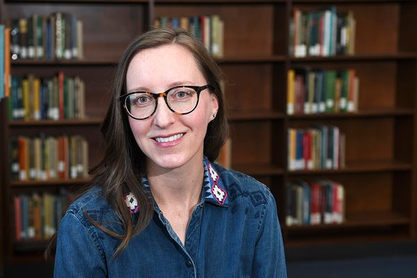 smiling woman in a library wearing glasses