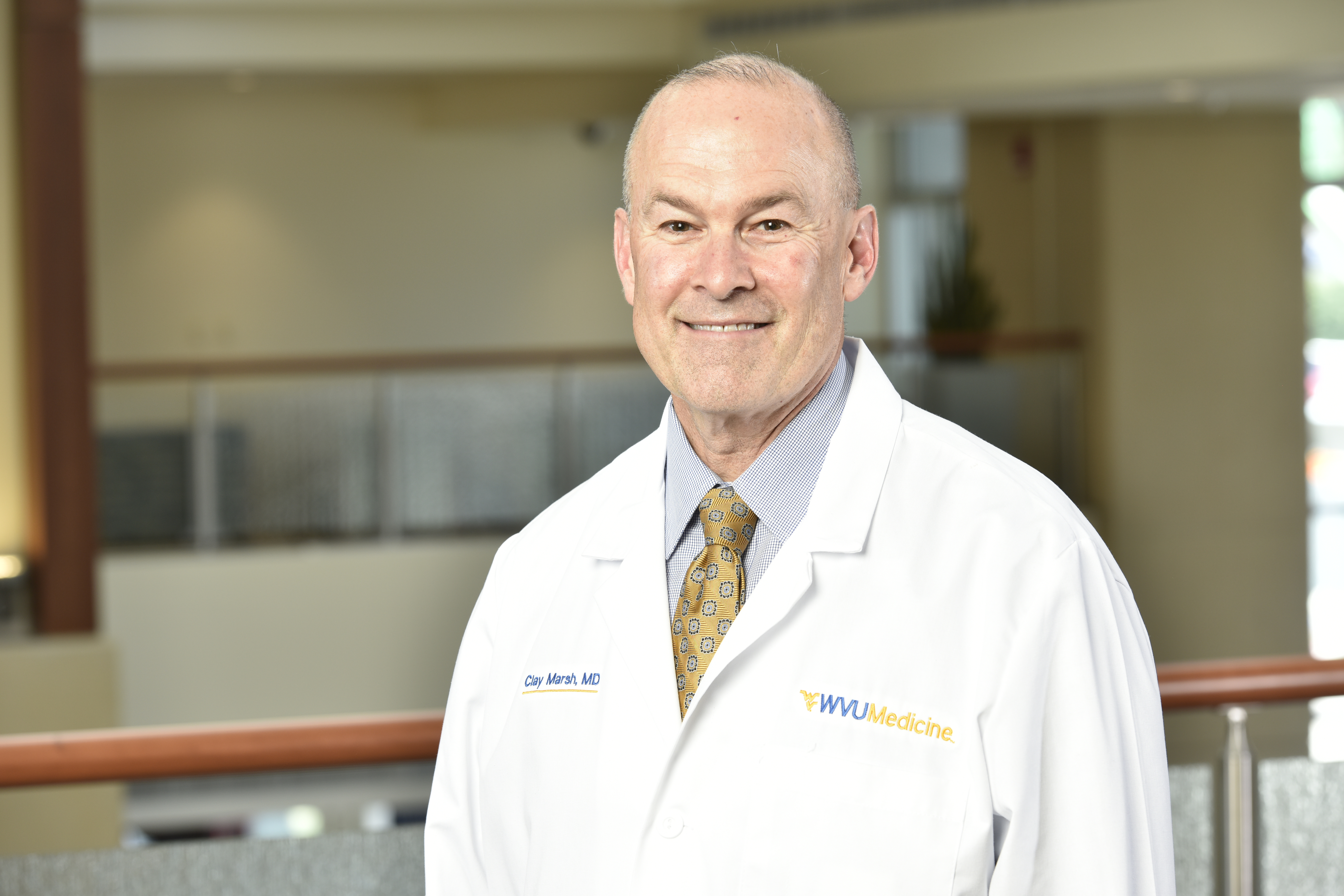 Photo of man with gray hair standing in WVU Medicine white lab coat