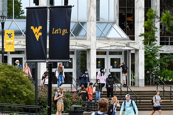 people walk down steps of large building, flying WV flag, Let's go flag in the foreground