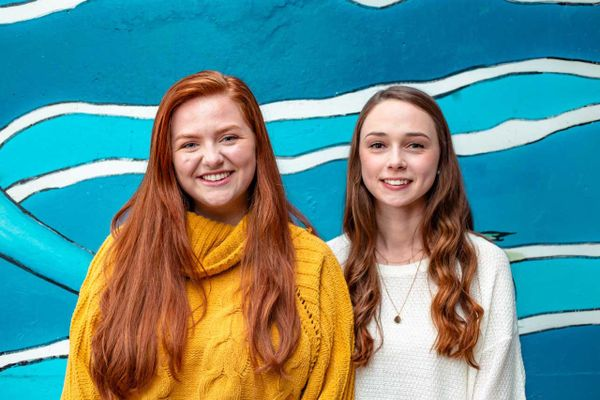 two girls with long hair in front of a blue, teal, aqua and white background