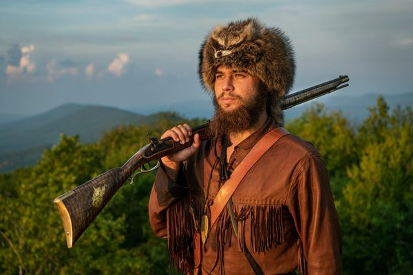 young man in buckskins, coonskin cap, musket over his shoulder, mountains in background