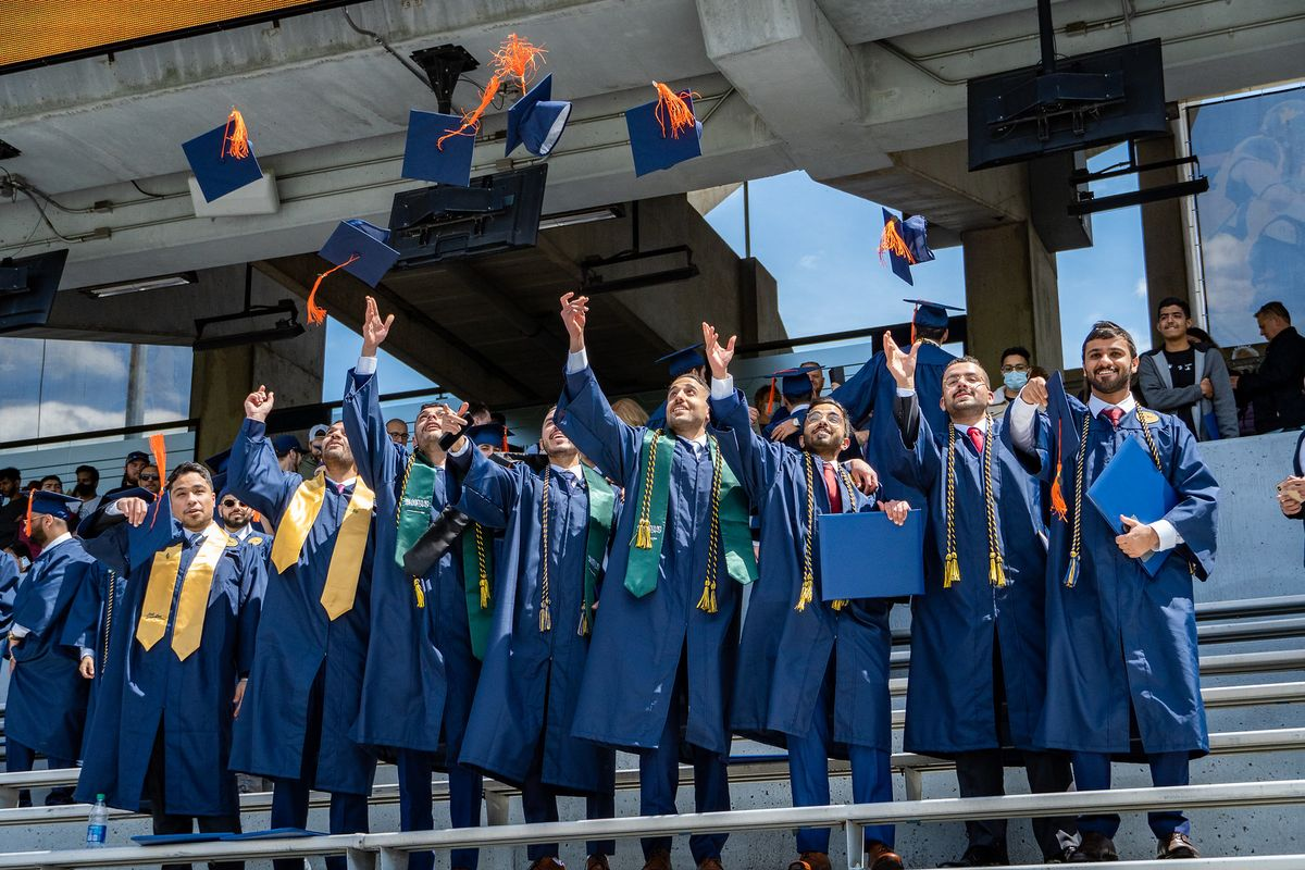 students in caps and gowns toss their mortar boards into the air