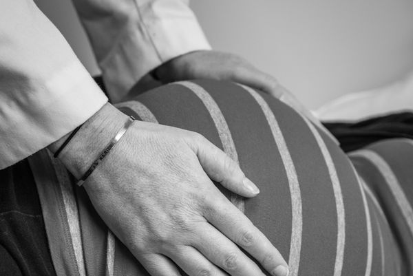 Two hands touch a pregnant belly
