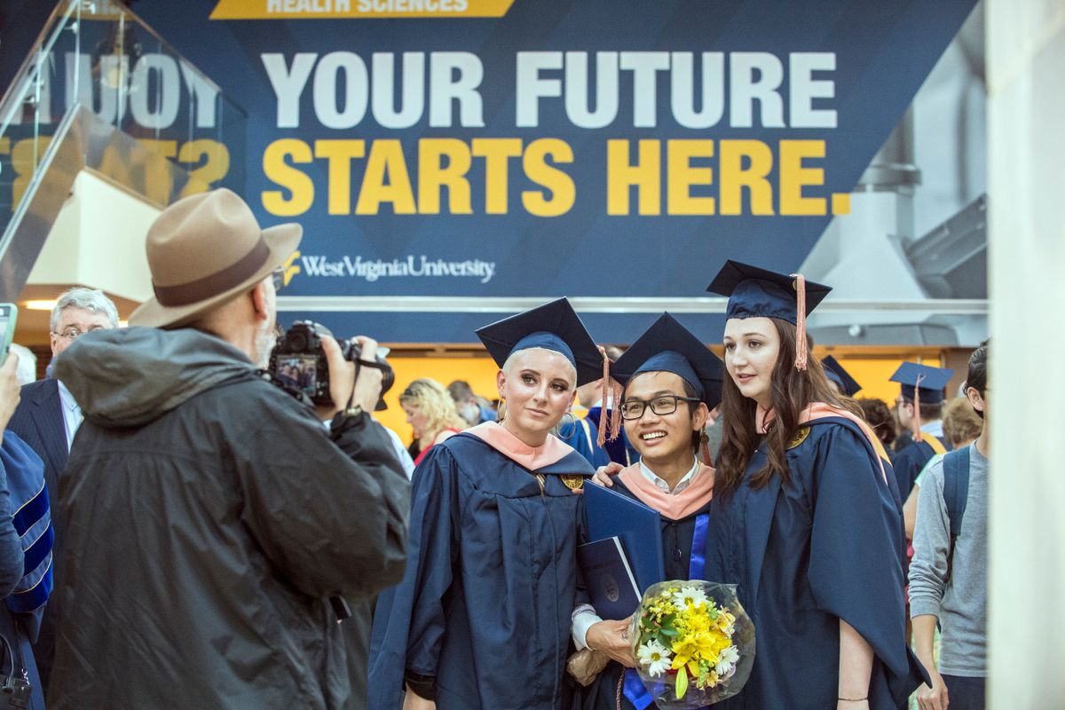 Man in a brown hat takes a picture of smiling students wearing blue caps and gowns on graduation day