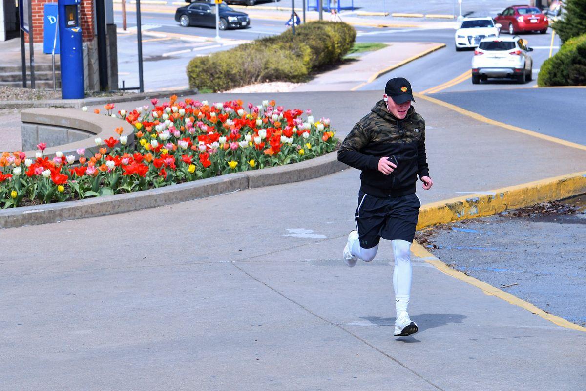 man in shorts, leggings, cap runs on an empty sidewalk