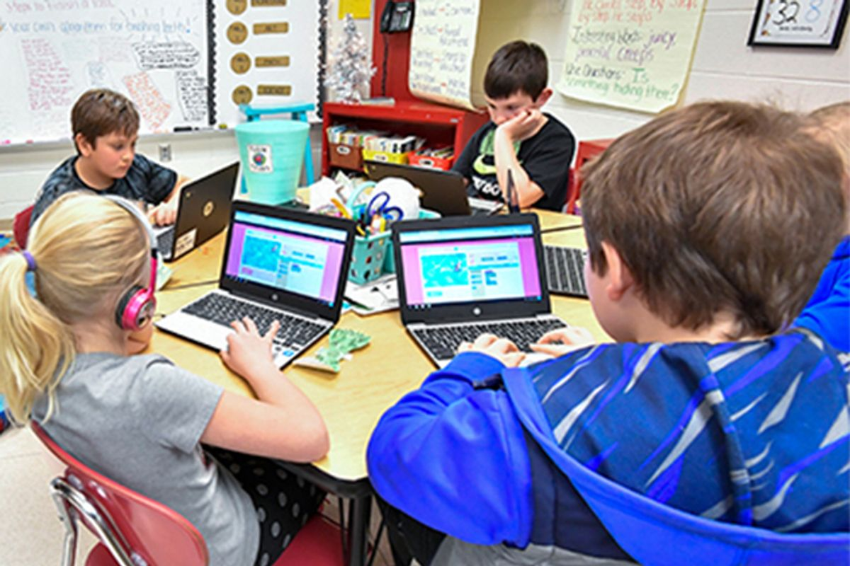 Elementary school students using tablets sit at a round table