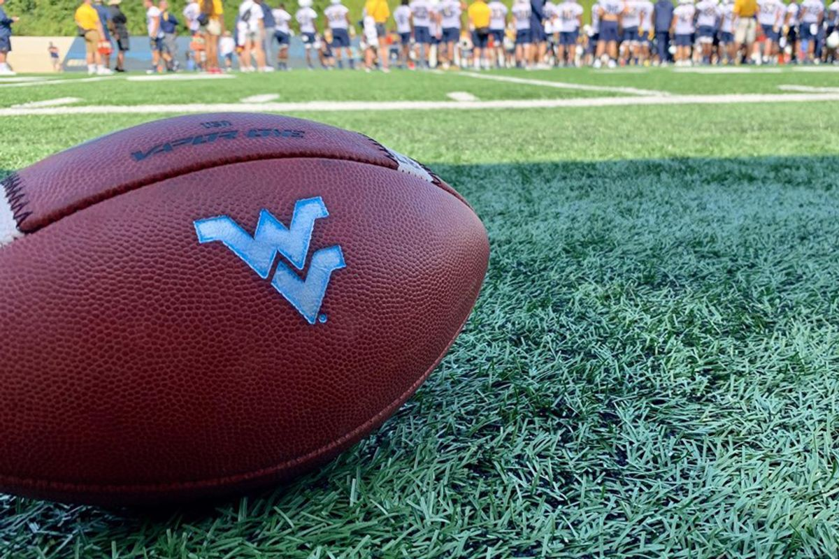 football in grass, flying WV emblem