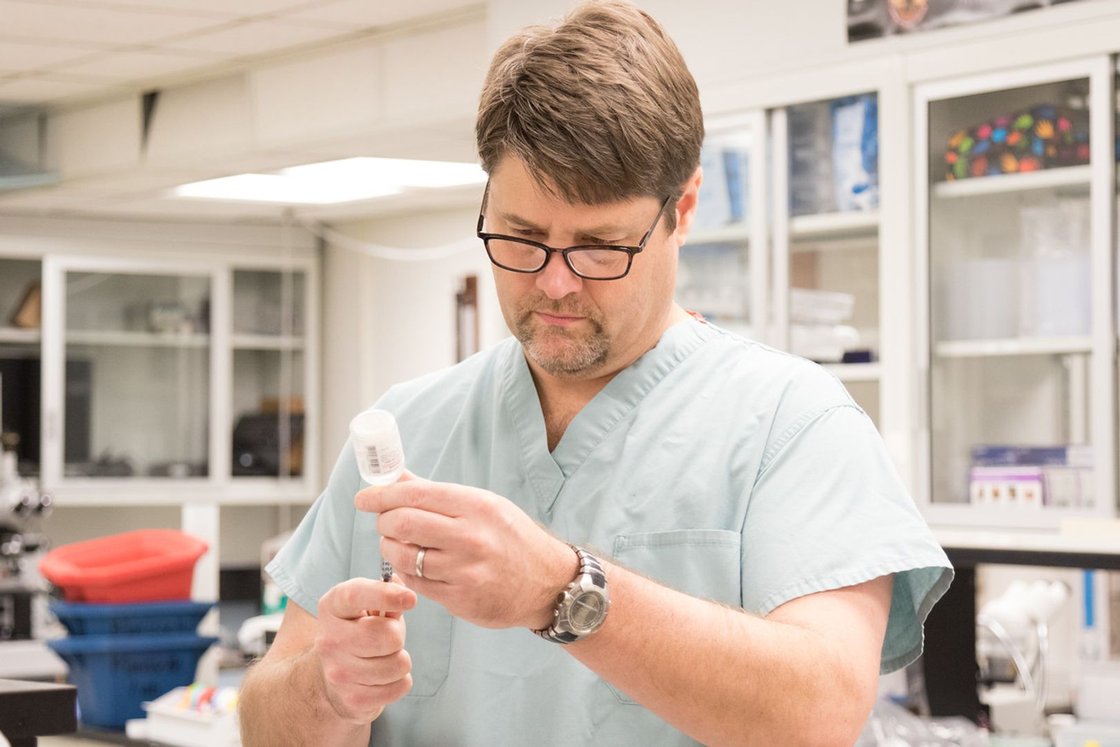 man stands with vial and syringe in hand in a lab