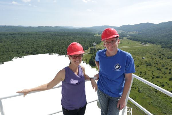 two people in red hard hats stand on a white object far above ground