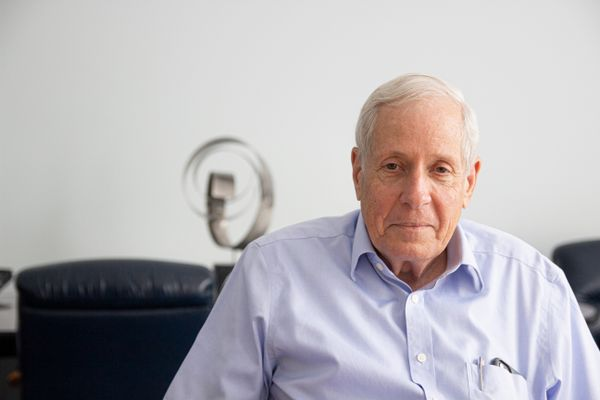 Older gentleman in a blue button down poses for a headshot with a couch and a sculpture in the background.