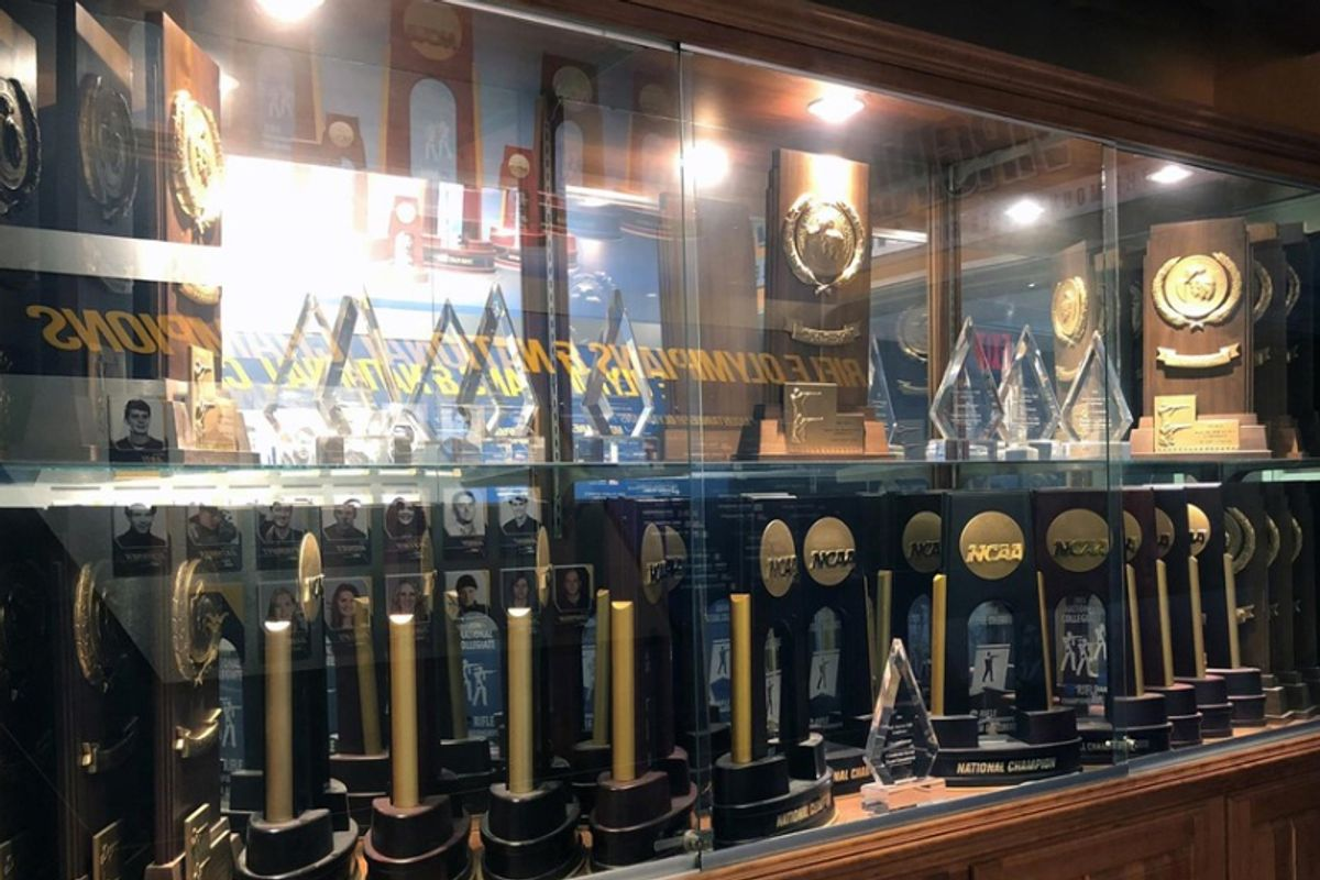 WVU rifle team trophies and awards in display case behind glass