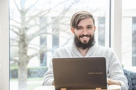 young bearded man with laptop