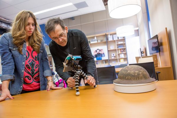 Joel Beeson and a student photograph a WWI soldier's helmet