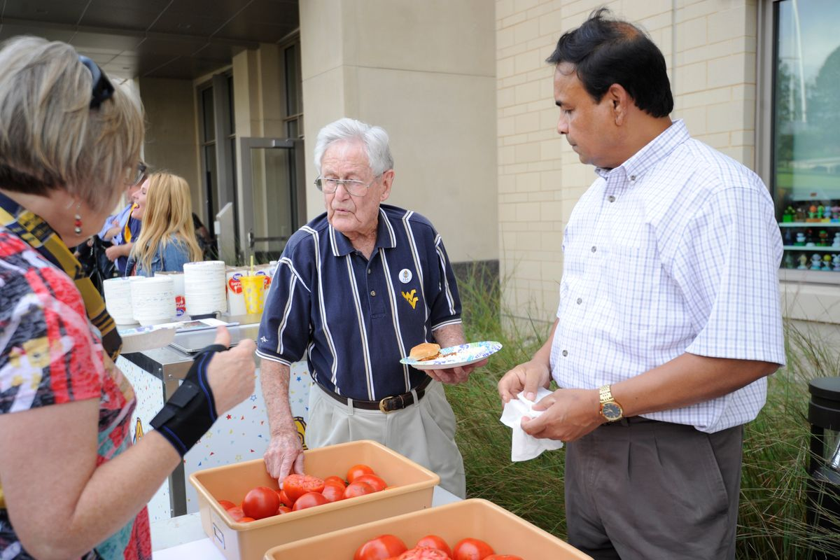 Students, alumni and faculty come together behind the Agricultural Sciences Building on the Evansdale Campus to celebrate the Davis College's and the university's 150th anniversary with a barbecue August 31, 2017. The college also came together to celebrate the naming of the two new tomatoes species created at WVU: West Virginia '17A (Mountaineer Delight) and West Virginia '17B (Mountaineer Pride.)
