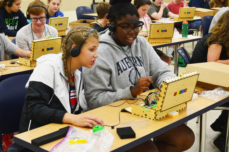 Two girls work on a coding project