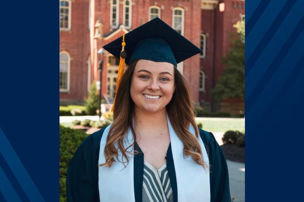 Woman in a navy graduation gown and cap