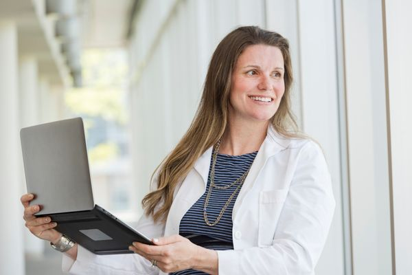 photo of smiling woman in white coat holding a tablet