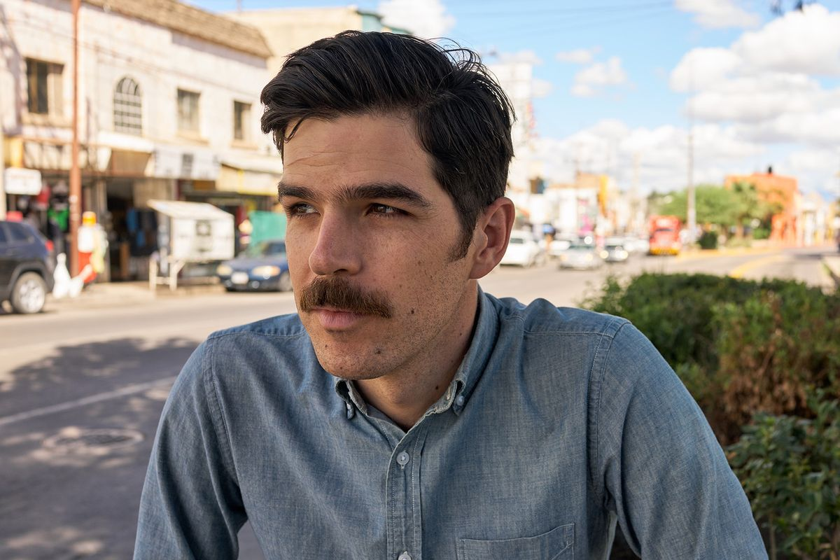 Man with mustache standing on street