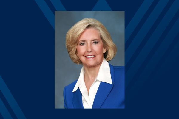Photo of white woman in blue suit on blue background