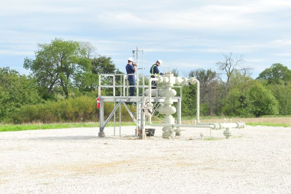 two men in hardhats and coveralls stand on gas well structure