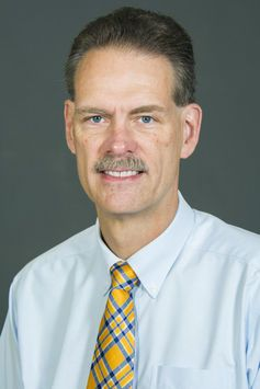 Headshot of man with gray hair and gray mustache in light blue button down and yellow and blue plaid tie.