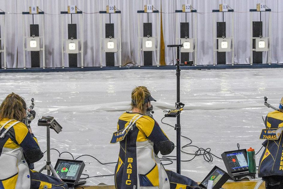 Three blonde women in WVU rifle team uniforms shoot at targets