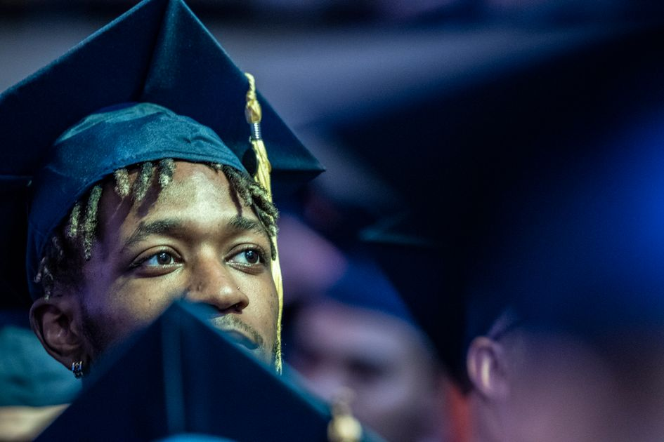Student attends WVU Commencement in blue cap and gown.
