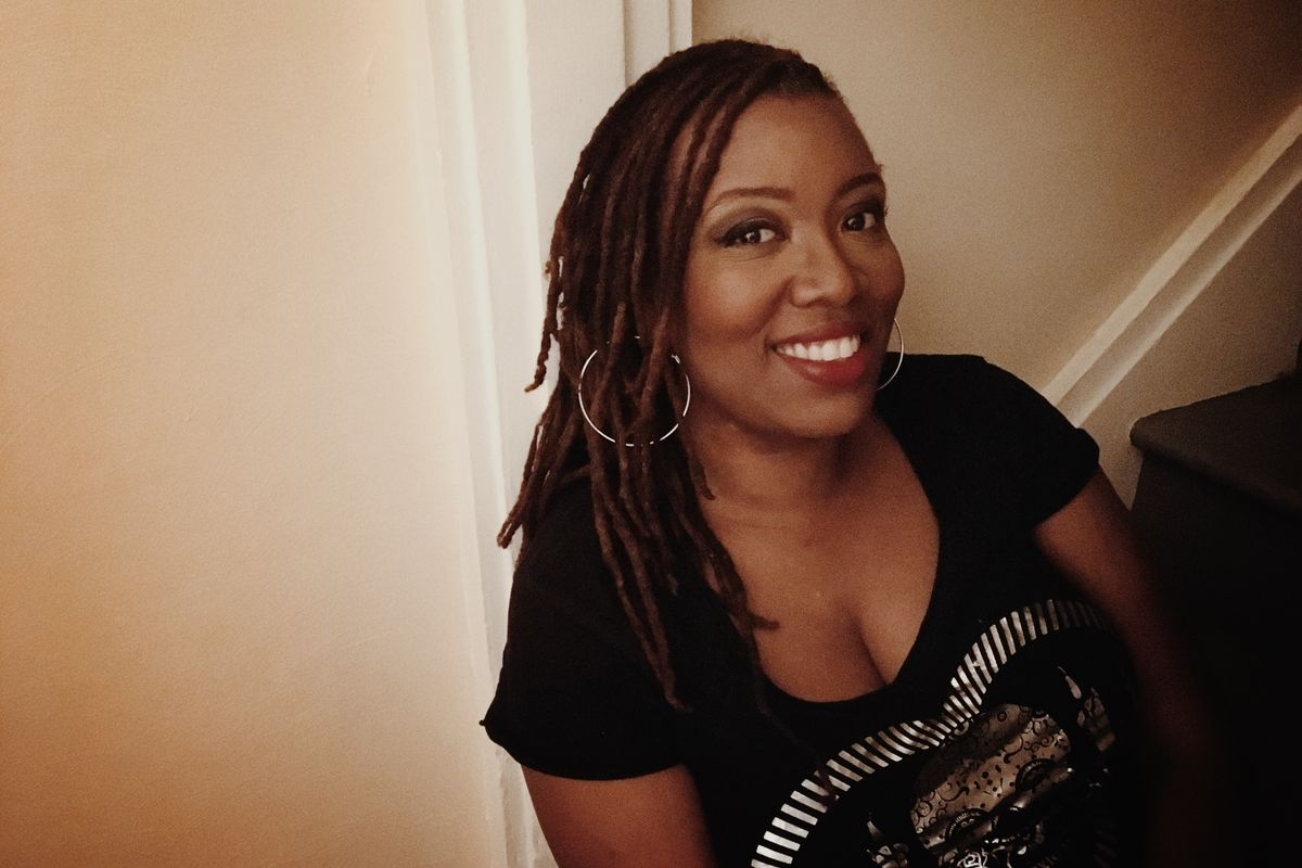 smiling black woman in black shirt sitting on staircase