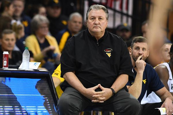 Bob Huggins sits on a stool on the basketball court wearing a black pullover shirt. His hands are clasped at his waist.