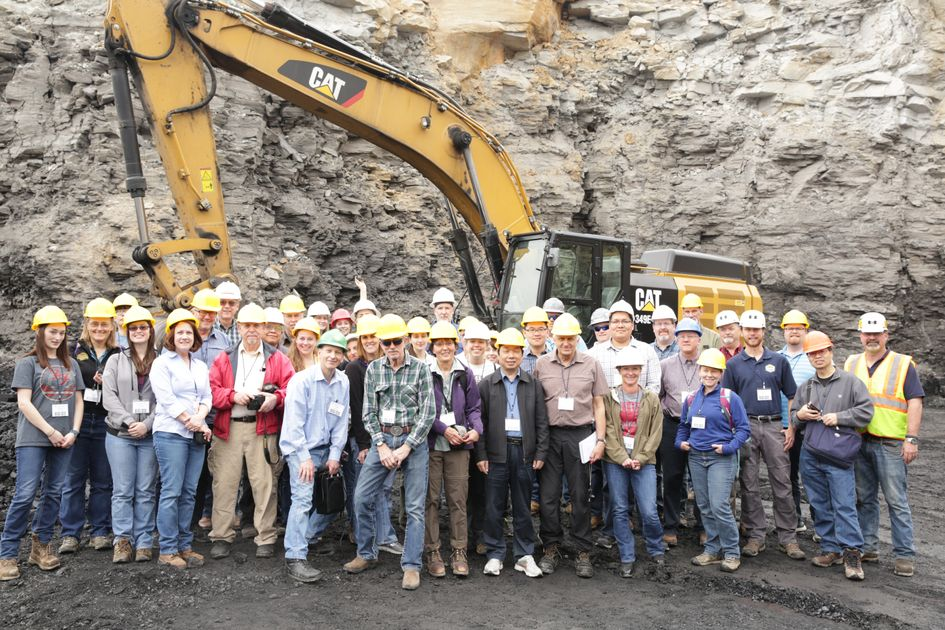 2017 Mine Drainage Symposium gathering in front of a high wall and heavy equipment