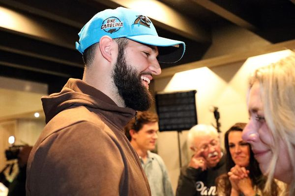 man with a dark beard wearing a light blue hat and brown hoodie smiles at a blonde woman