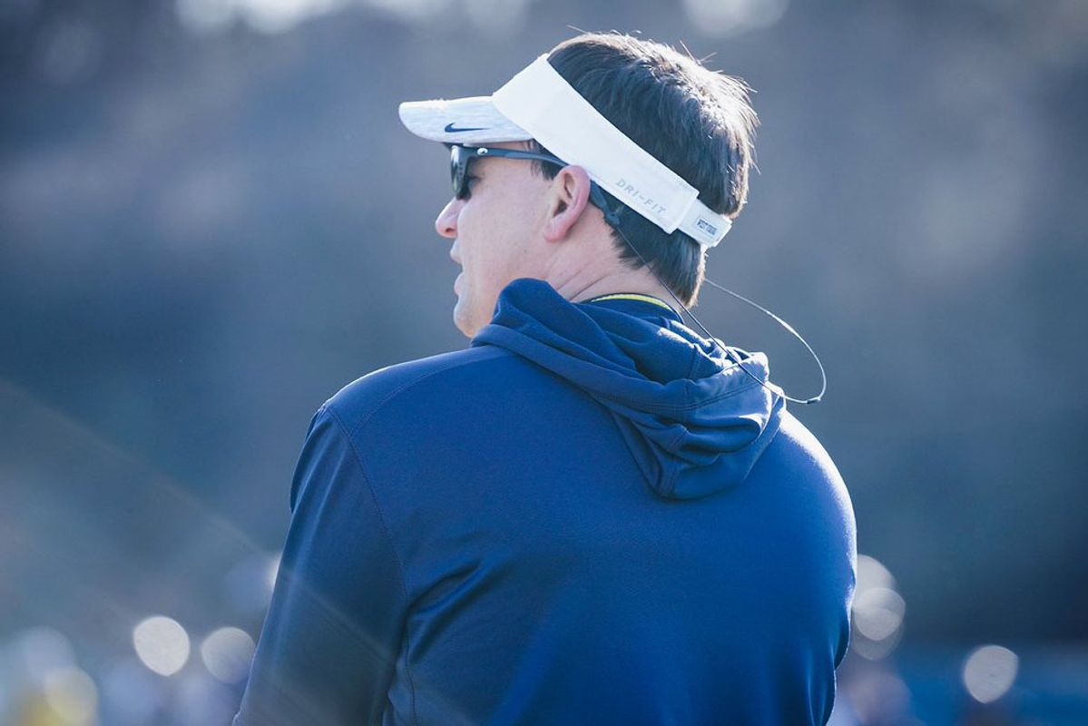 WVU football coach Neal Brown oversees practice in a white visor and blue hoodie.