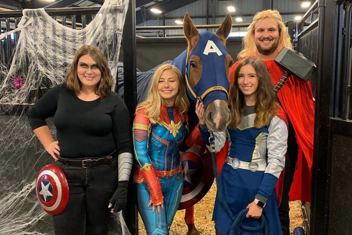Four people posed with a horse smiling