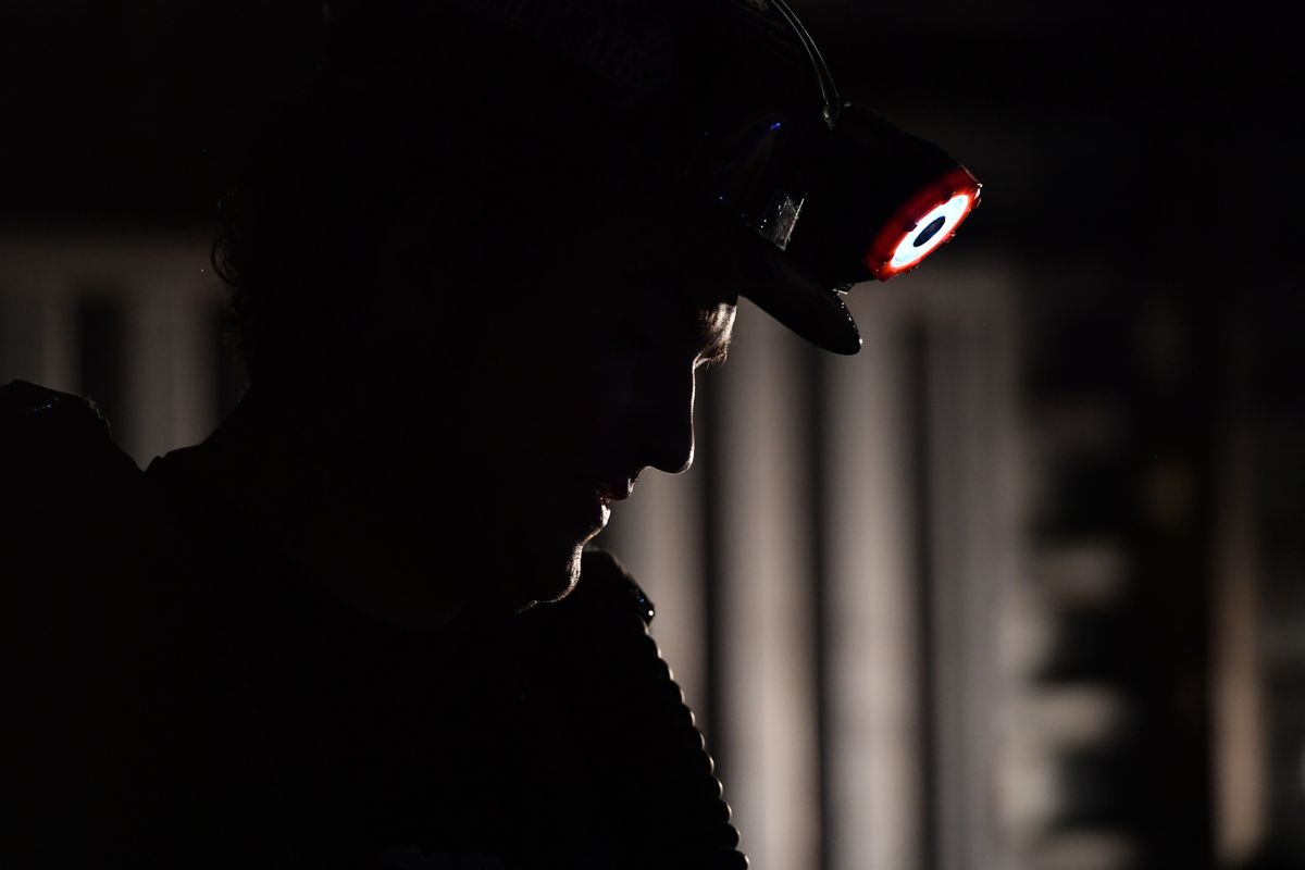 person in shadows wearing miner's hat with light