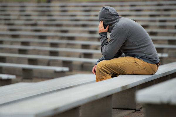 Man in a hoodie, sits alone
