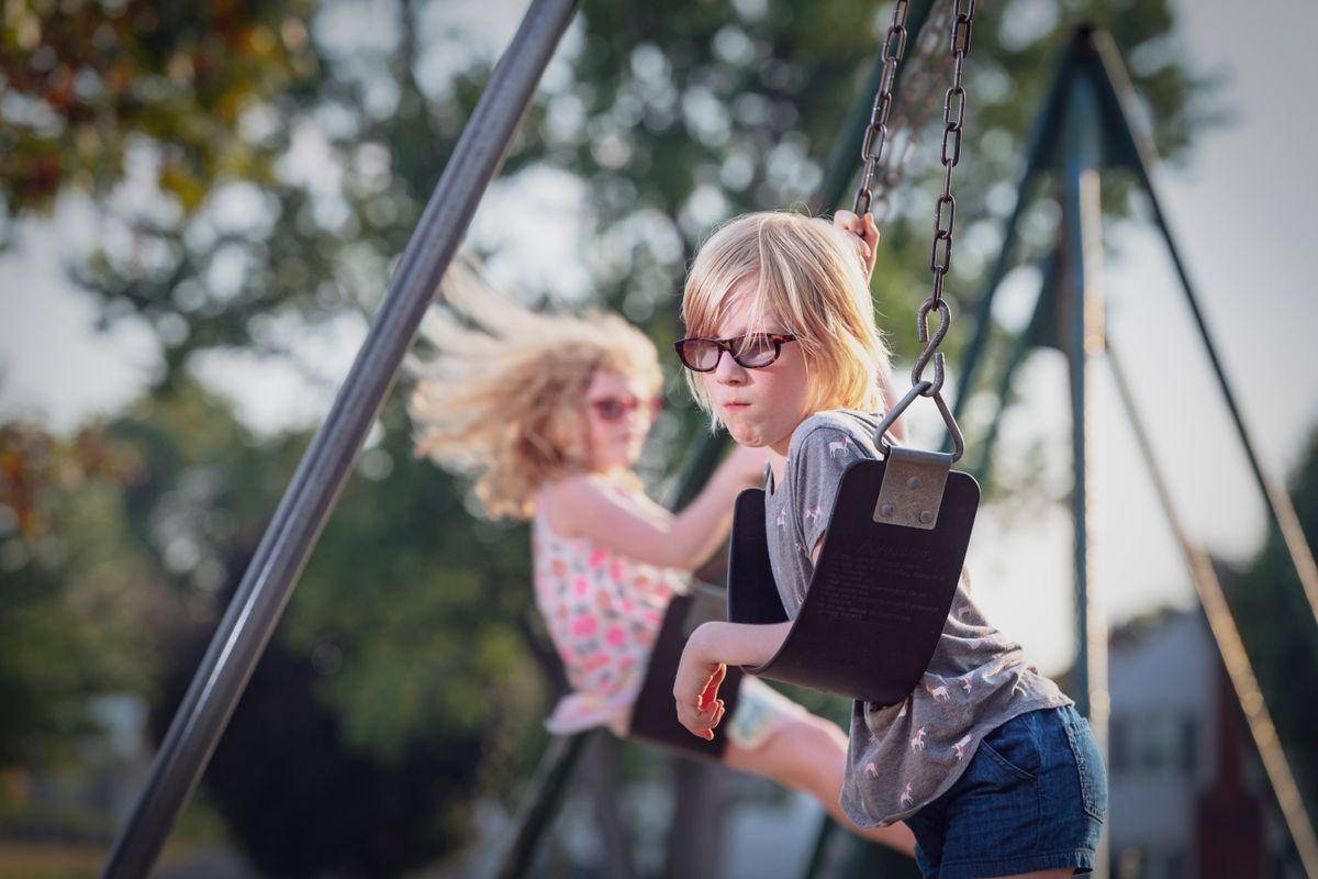 photo of two girls on swings