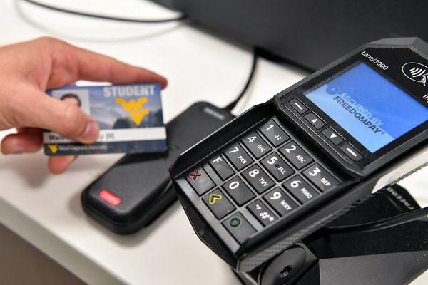 hand holds an id card next to a swipe machine