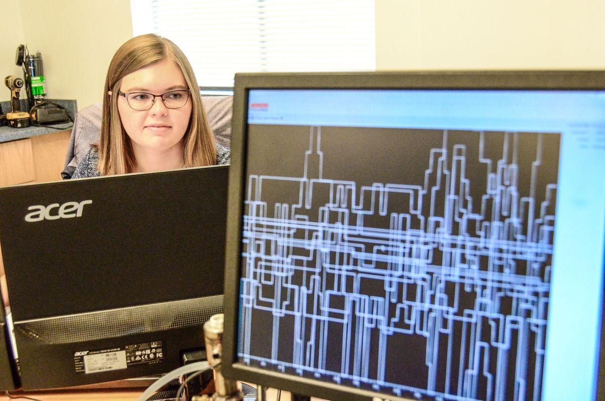 blonde woman with glasses looking at graphic on computer screen